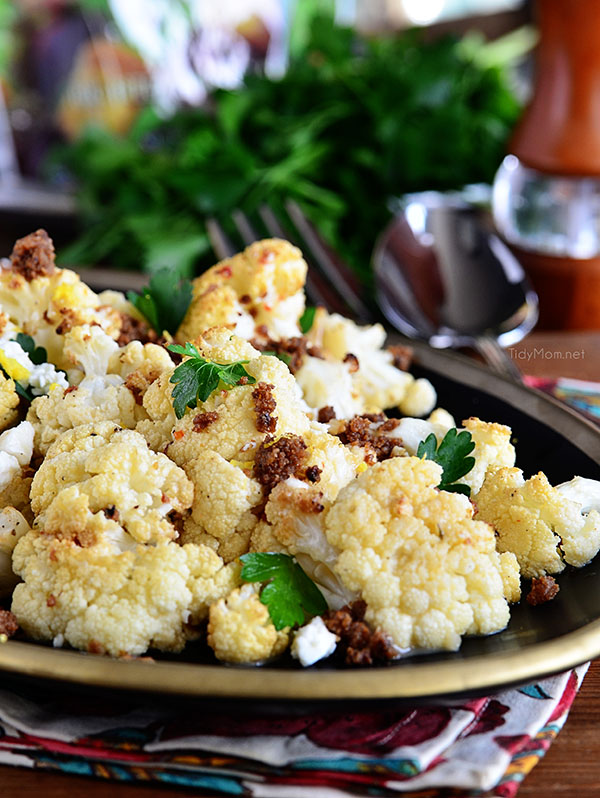The BEST Roasted Cauliflower recipe at TidyMom.net with Italian dressing, feta cheese and browned butter crouton crumbs