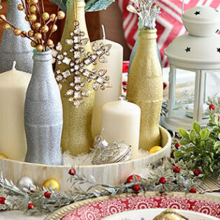 Use recycled Cocoa Cola bottles as a pretty holiday table centerpieces. Just paint with glitter spray paint and add some holiday florals, and arrange on a tray. Easy and costs almost nothing! details at TidyMom.net