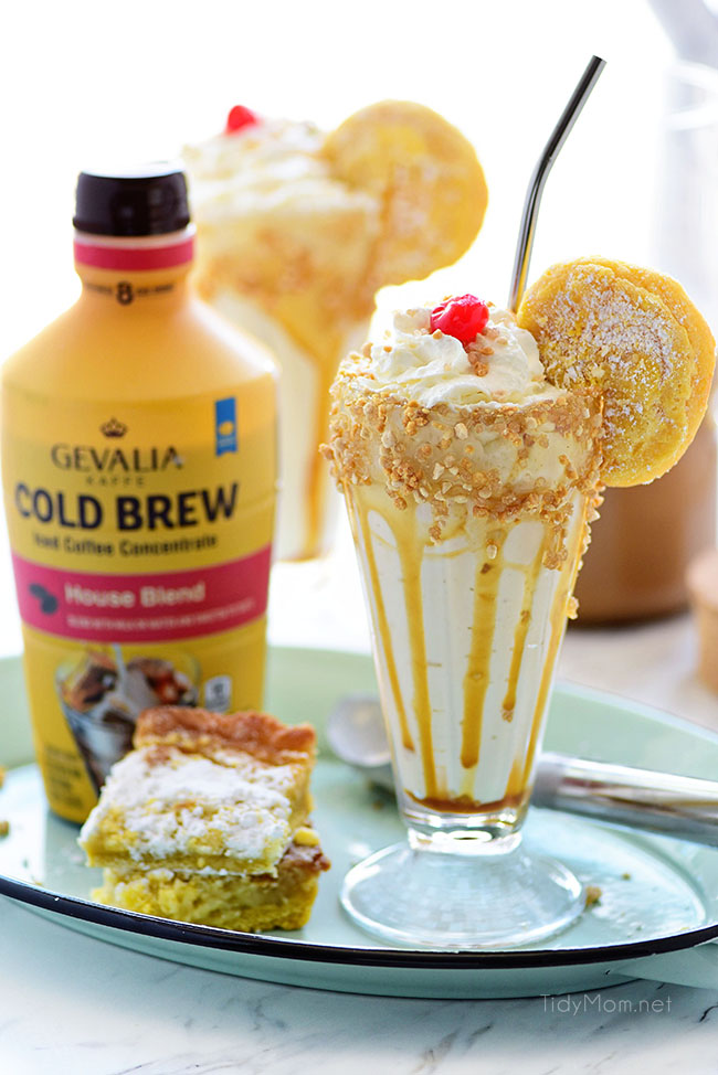 Gooey Butter Cake Cold Brew Milkshake in a glass with straw and bottle of Gevalia Cold Brew Concentrate and gooey butter cake on tray.