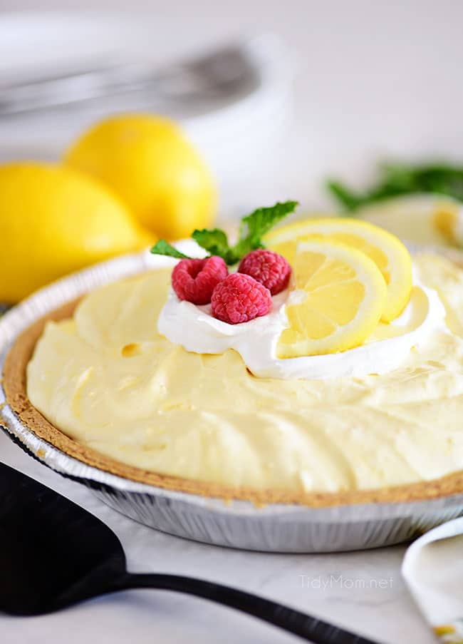 Cold lemonade pie garnished with lemon slices and raspberries