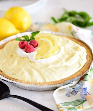 lemonade pie in a graham cracker crust and topped with lemon slices and fresh raspberries