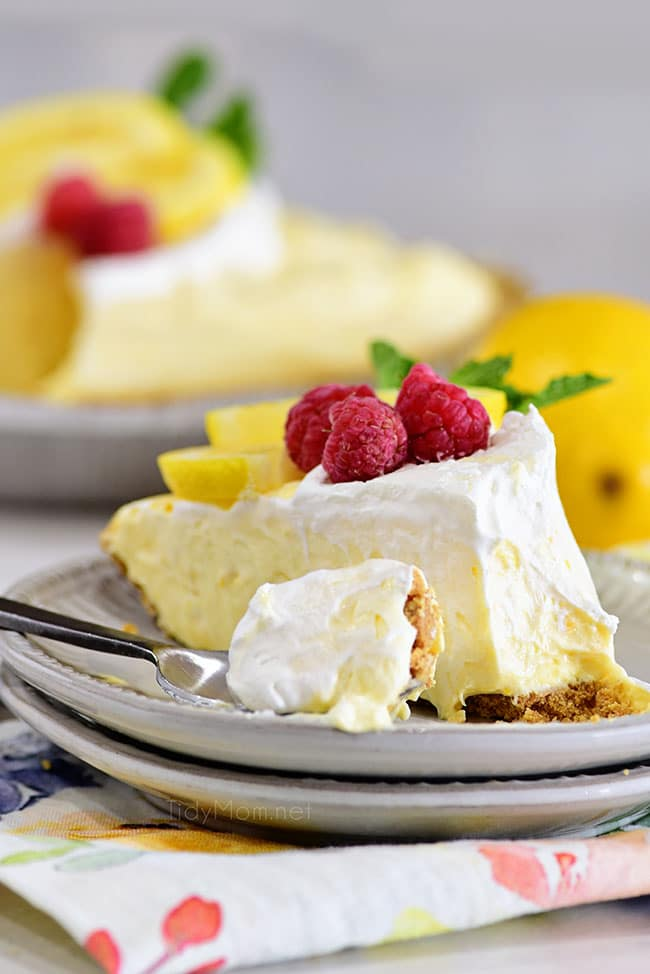 a slice of lemonade pie on a plate with a bite of the pie on a spoon