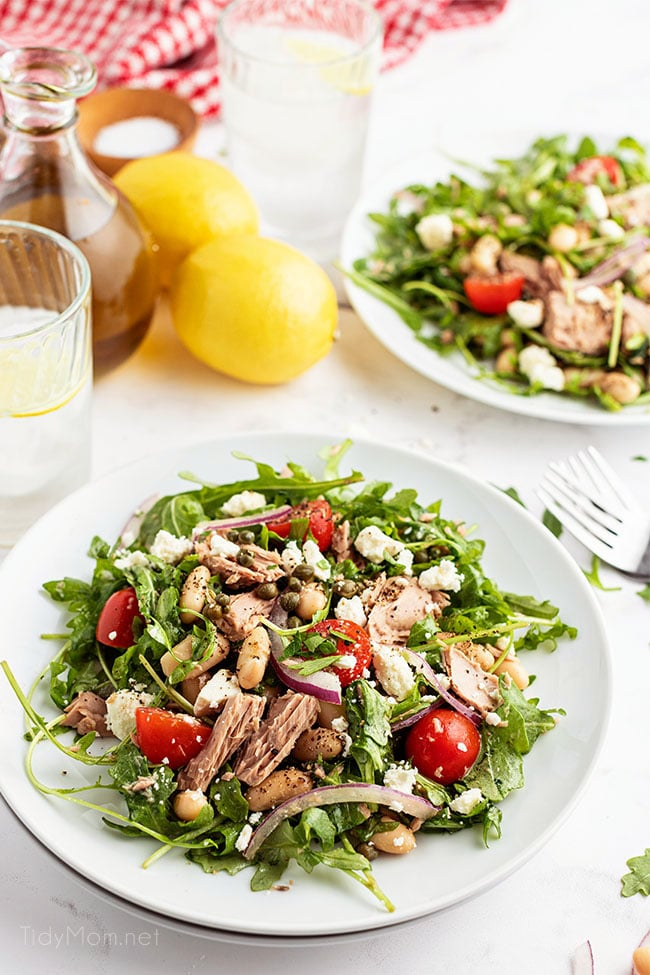 two plates of salad with a fresh lemon on the counter