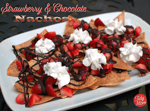 A clever twist on nachos! Dessert Nachos with strawberries and chocolate piled on sweet and crunchy cinnamon chips will be the hit of the party! Print full recipe at TidyMom.net