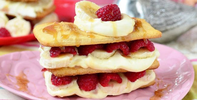 Napoleon dessert recipe with raspberries, bananas and caramel sauce on pink plate