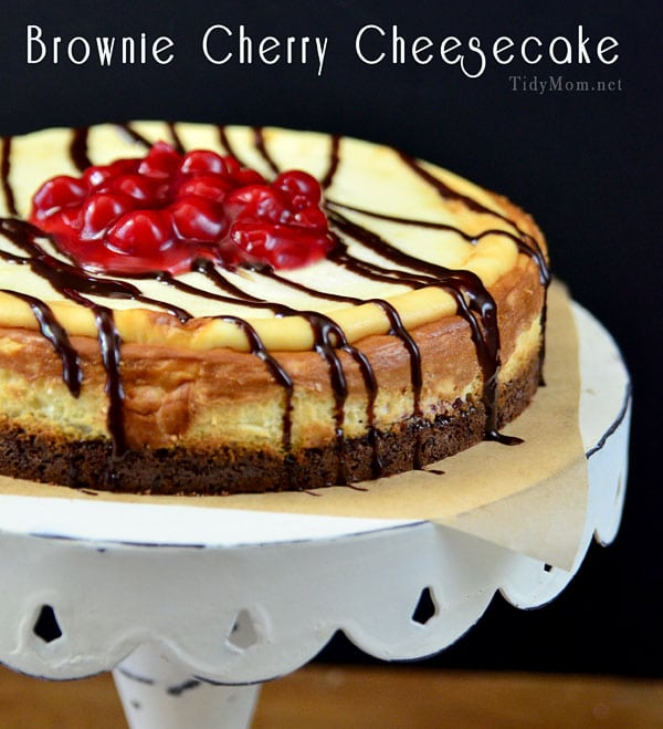 This Brownie Cherry Cheesecake starts with a fudgy brownie crust, and is topped with cherry pie filling and cheesecake. The BEST cheesecake for any brownie lover!  Print the recipe at TidyMom.net #cheesecake #brownies #cherry #dessert