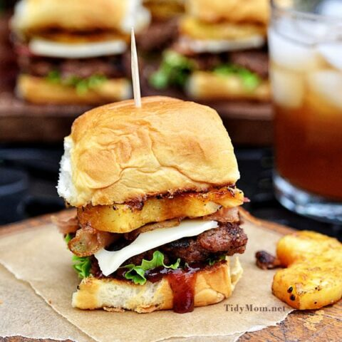 Fire up the grill this summer for this mini Hawaiian burger recipe. Aloha BBQ Sliders are flavored with barbecue sauce and served on sweet rolls with cheese, pineapple and bacon.