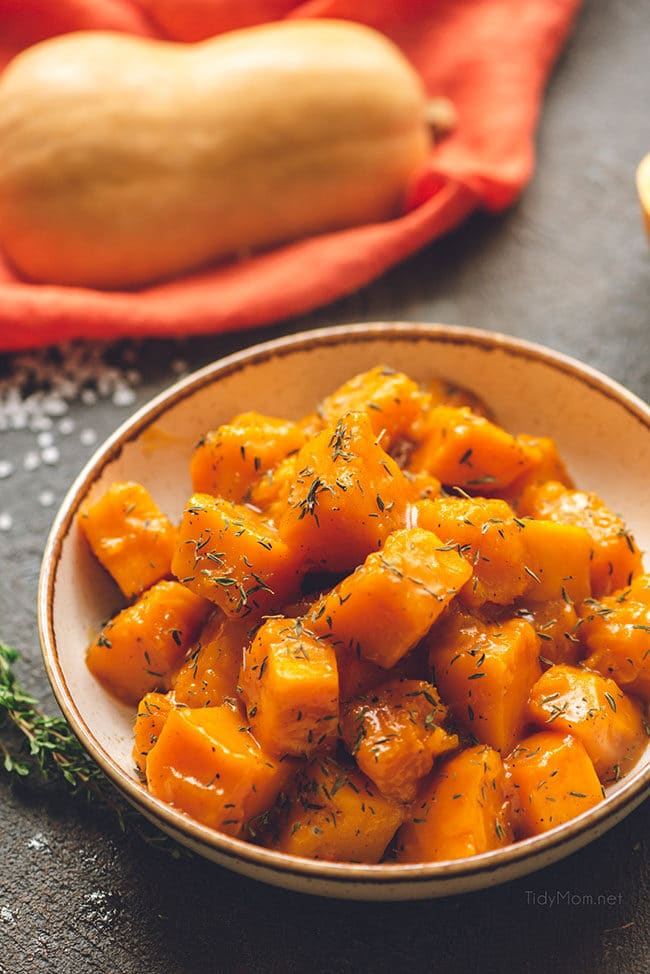 maple braised butternut squash in a bowl seasoned with fresh thyme in a bowl