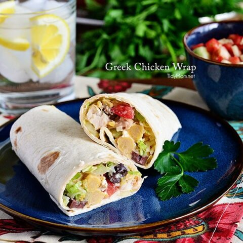 This Greek Chicken Wrap is stuffed with garbanzo beans, chicken, feta cheese, tomatoes, and cucumbers are rolled in tortillas for a quick Greek-inspired lunch. Print recipe at TidyMom.net