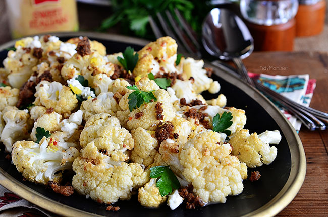 Roasted Cauliflower with feta cheese and browned butter crouton crumbs on a black plate