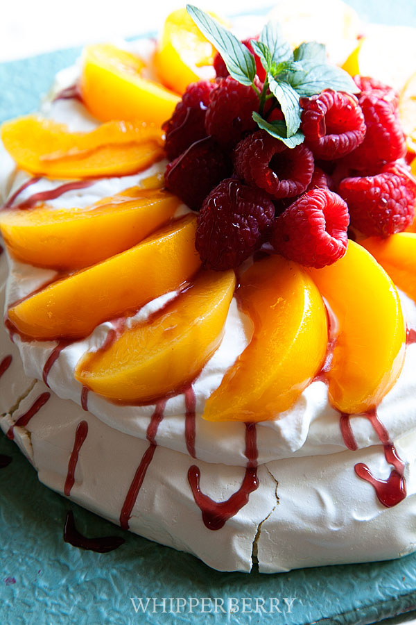Peach Melba Pavlova topped with fresh summer fruit