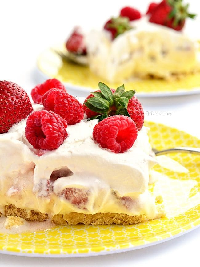 no-bake strawberry cheesecake dessert topped with fresh berries on yellow plates