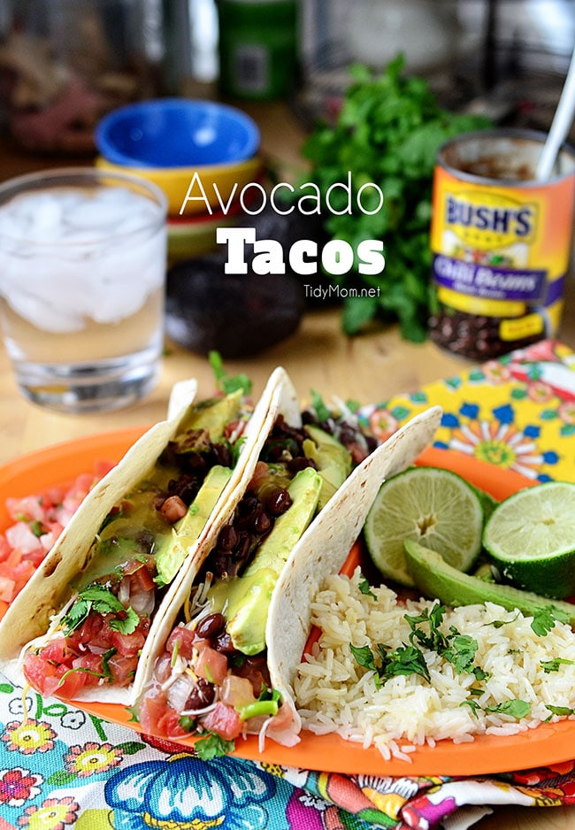 These avocado tacos come together in minutes and make a delicious weeknight meal. Avocado and black beans are folded into warm tortillas, topped with shredded cheese and guacamole and drizzled with tomatillo sauce. Print recipe at TidyMom.net #tacos #tacotuesday #beans