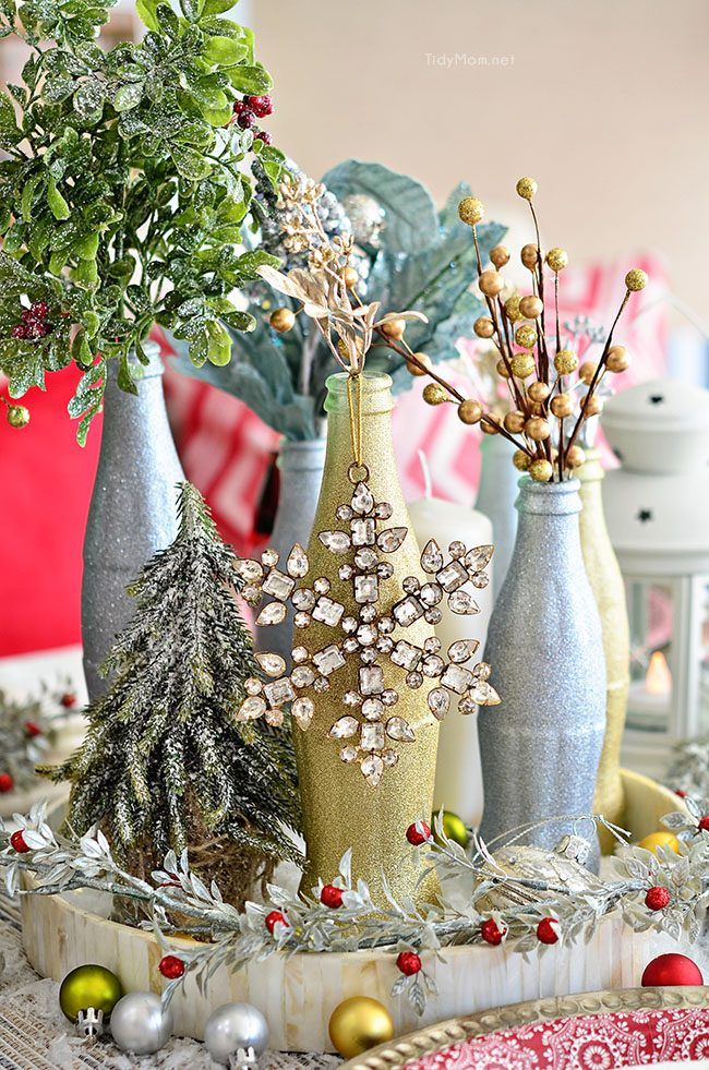 Use empty Cocoa Cola bottles as a pretty holiday table centerpiece. Just paint with glitter spray paint and add some holiday florals, and arrange on a tray. Easy and costs almost nothing! details at TidyMom.net
