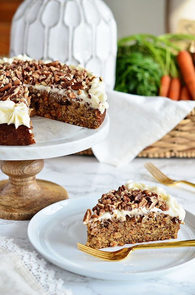 carrot cake on cake stand and cut piece on plate