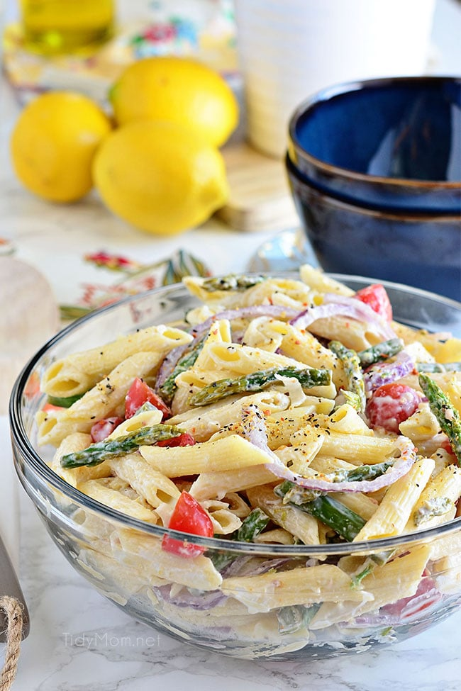 pasta salad in a bowl with lemons in background