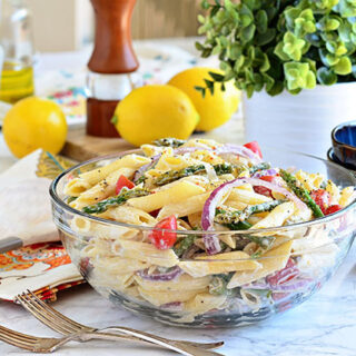 a glass bowl filled with pasta salad