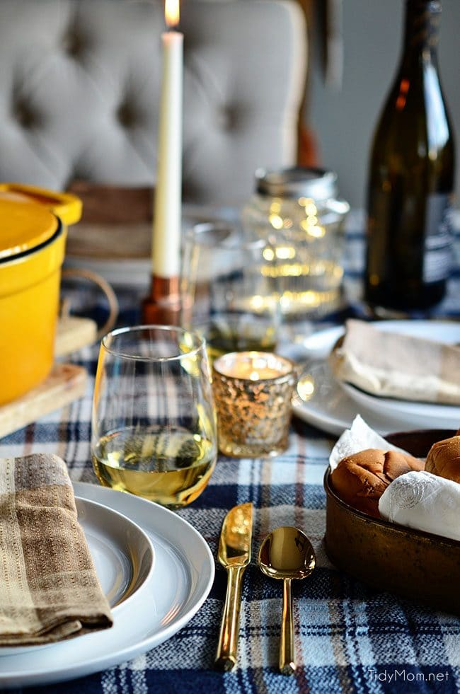 Set a simple cozy dinner table with a blanket, candles, lights and music.