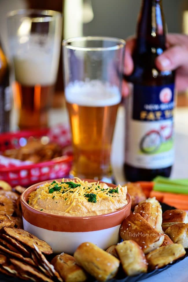 Pub-style Beer Cheese Dip with pretzel and glass of beer.