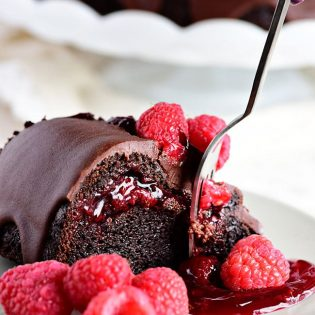fork going into a slice of Chocolate Raspberry Bundt Cake with a surprise raspberry filling and a Chocolate Chambord Glaze