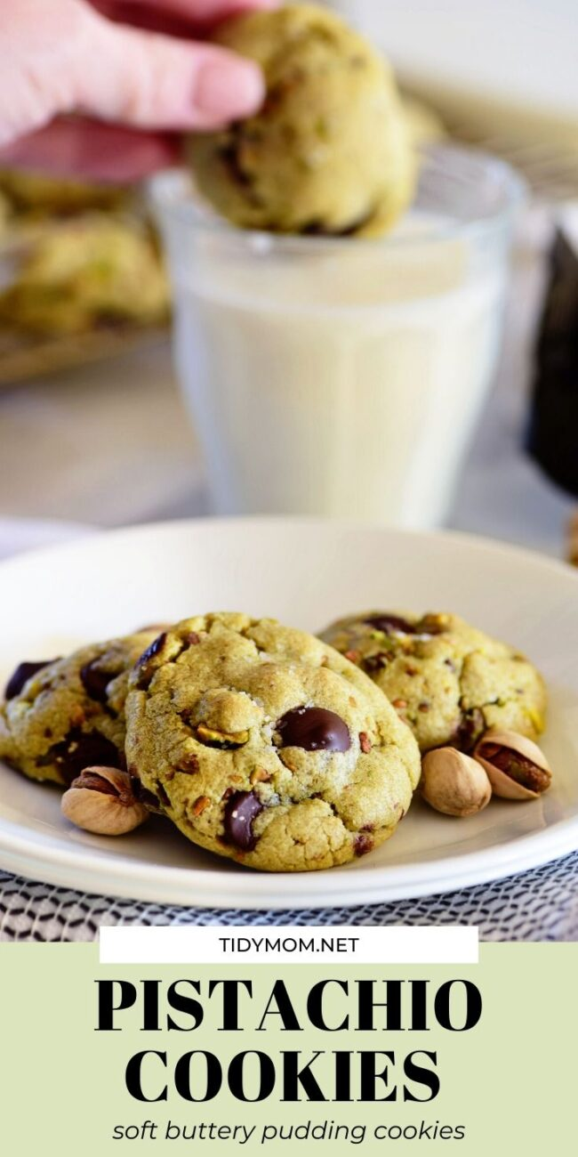 pistachio cookies on a plate and one being dunked in milk
