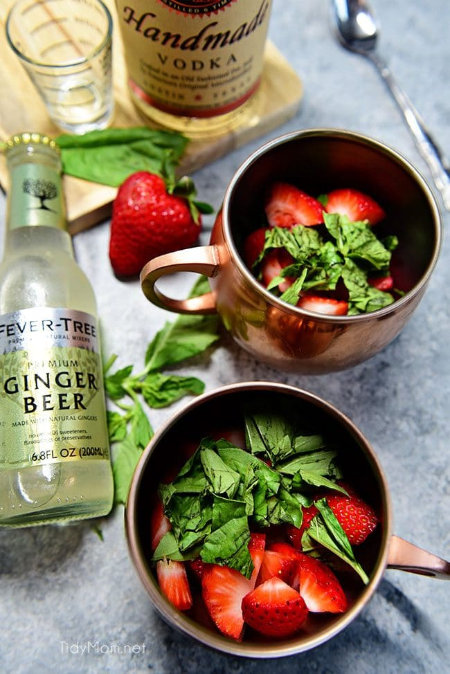 Strawberry Basil Moscow Mule is the perfect summer cocktail. Made like a traditional Moscow Mule with vodka, ginger beer and lime, with the addition of muddled fresh strawberries and basil. Print the recipe at TidyMom.net Delicious!