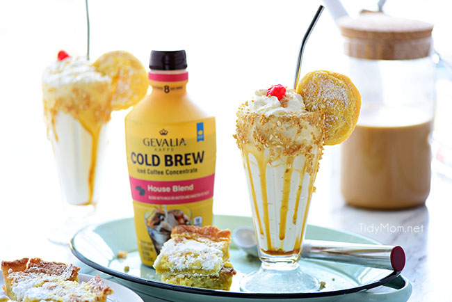 Gooey Butter Cake Cold Brew Milkshake in a glass with straw and bottle of Gevalia Cold Brew Concentrate and gooey butter cake and ice cream scooper on tray.