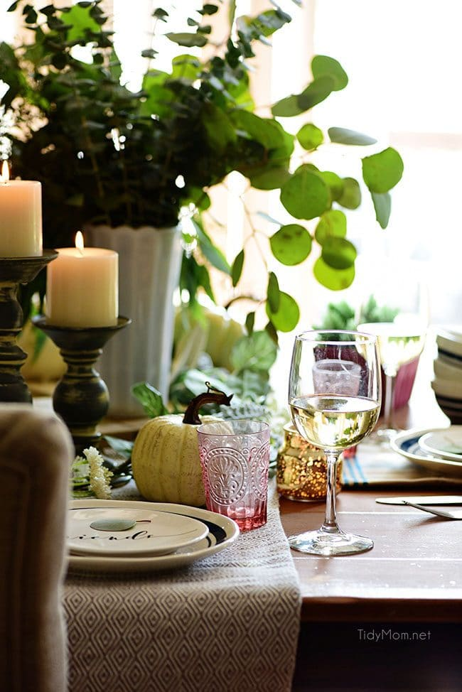Set table with light candles: Seasonal Simplicity — Blue and Green Fall Tablescape with simple eucalyptus and pumpkins fall centerpiece . Get all the details along with 20+ Fall Home Tours at TidyMom.net