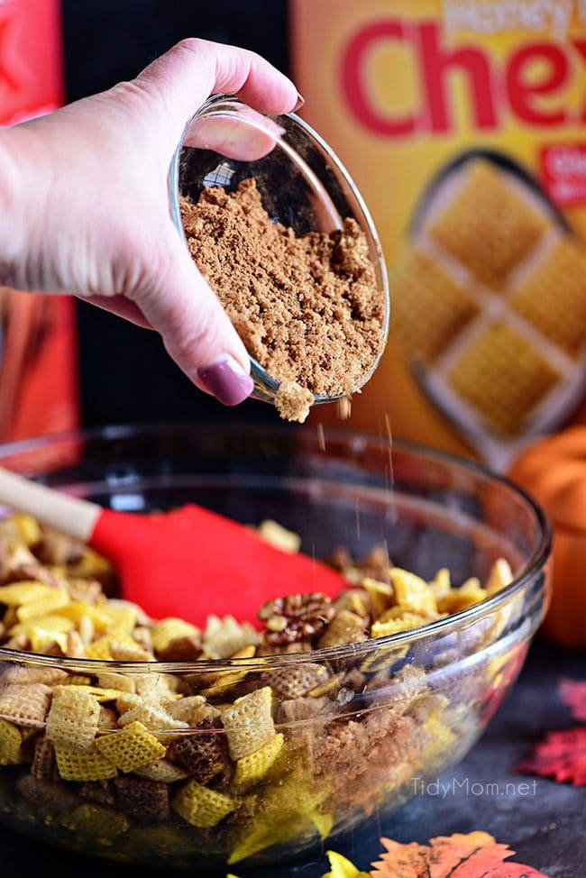 Adding sugar and spice to make Pumpkin Spice Chex Mix on pan