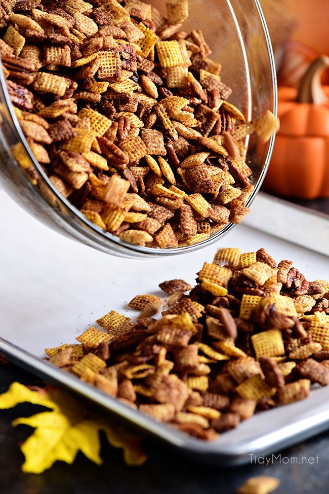 Pouring Pumpkin Spice Chex Mix on pan