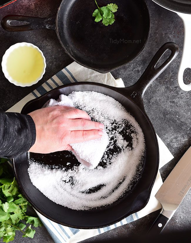 cast iron skillet being cleaned with salt and oil