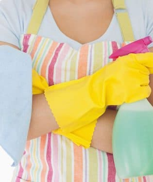 woman holding window cleaner and rag wearing apron and rubber gloves