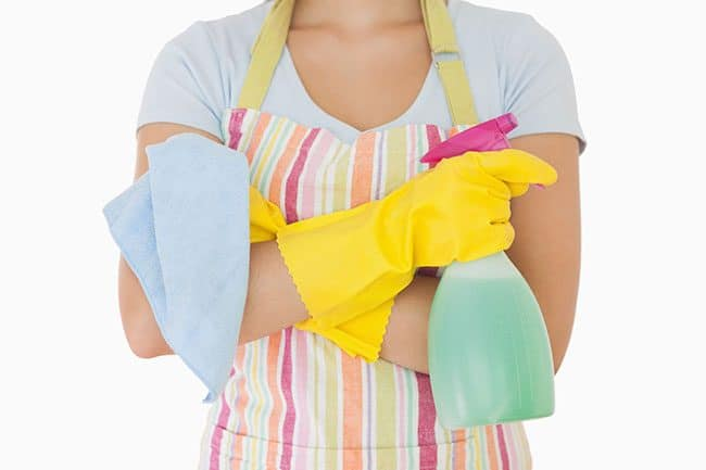 How to keep your house clean: woman holding window cleaner and rag wearing apron and rubber gloves