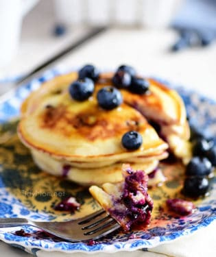 a stack of blueberry pancakes on a blue floral plate