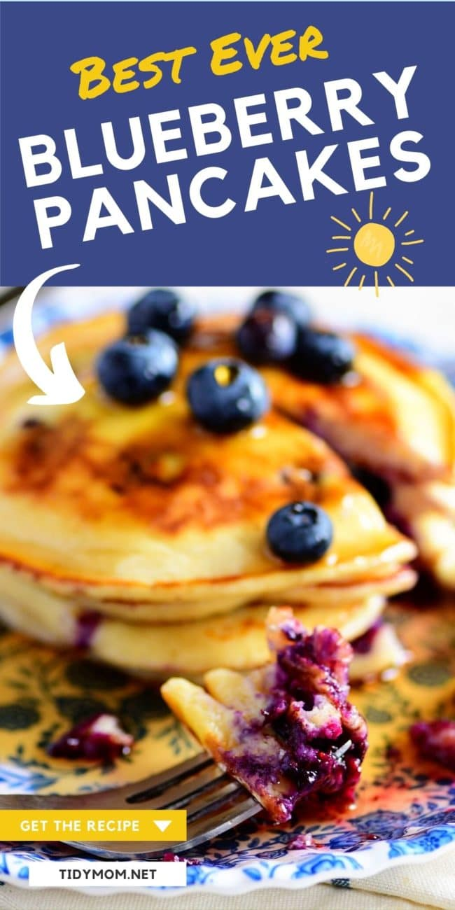a stack of blueberry pancakes with a bite on a fork