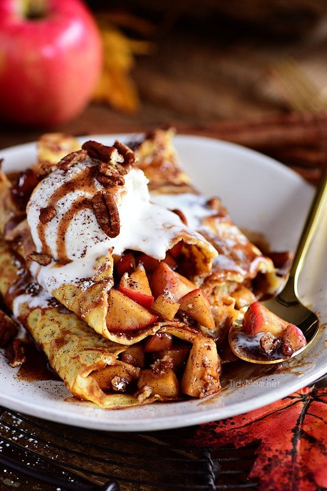 Apple Pie Crepes are thin french pancakes filled with a gooey caramel apple compote and toasted cinnamon pecans. Top with ice cream for the perfect dessert crepes.