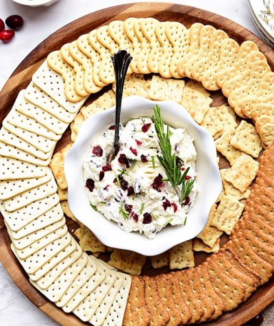 Cranberry Cream Cheese Dip with rosemary on a round tray with crackers