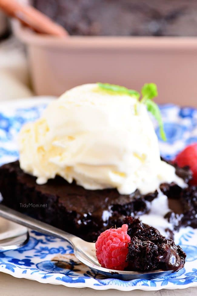 chocolate lava cake on a plate topped with ice cream and raspberries