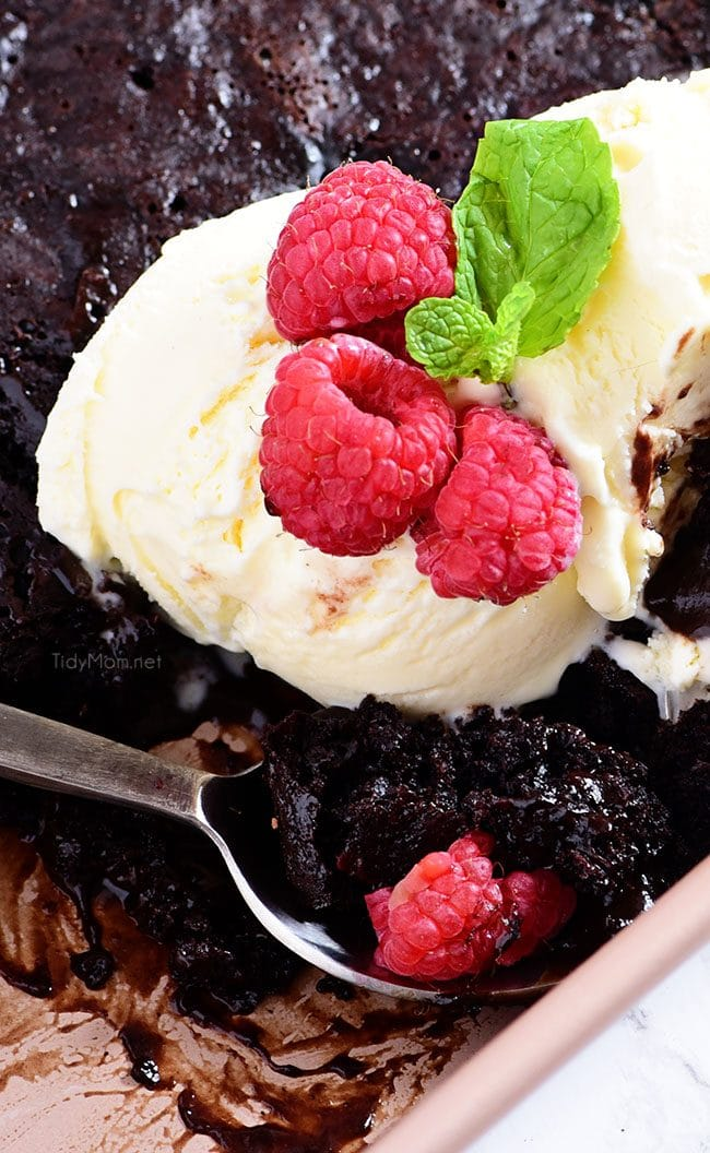 chocolate lava cake in the pan topped with ice cream and rasberries