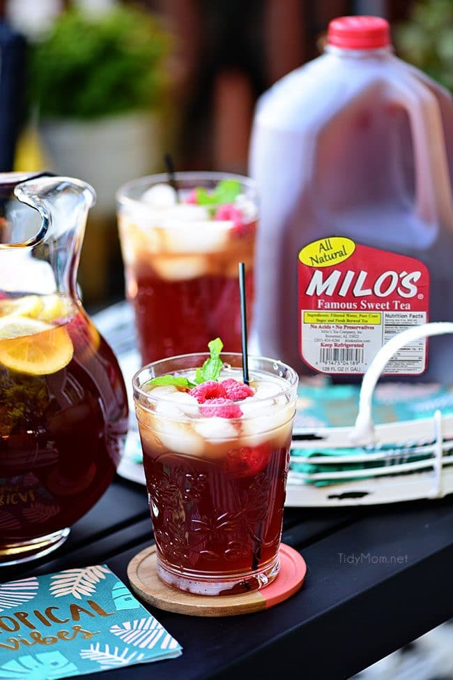Raspberry Hard Iced Tea Cocktail in a glass with a gallon jug of Milos Famous Sweet Tea