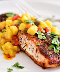 blackened salmon on a plate topped with mango salsa