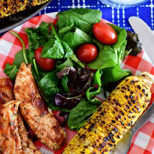 Chili Lime Corn On The Cob on dinner plate with BBQ chicken and salad