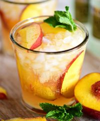 Ginger Peach Bourbon Smash cocktail on a board with a peach