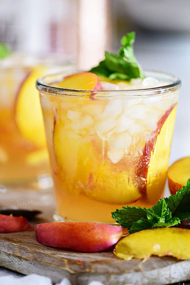 Ginger Peach Bourbon Smash cocktail on cocktail board with fresh peaches