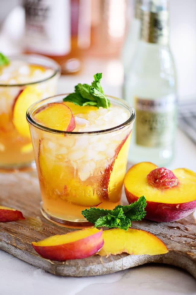 Ginger Peach Bourbon Smash cocktail on board with fresh peaches
