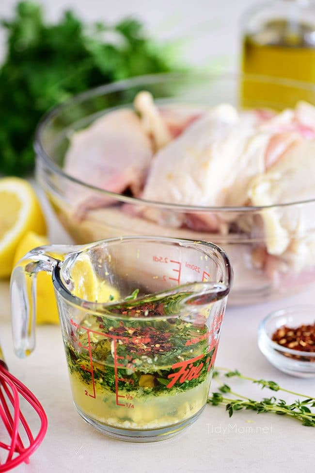 lemon herb chicken marinade in measuring cup with raw chicken