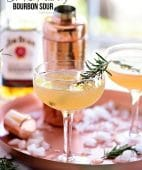 Bourbon Sour with smoked rosemary in coupe glasses