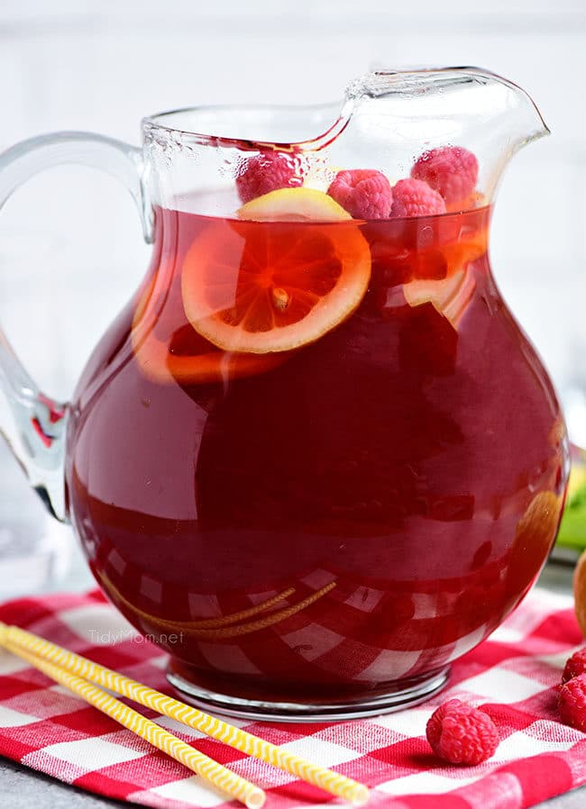 A pitcher of Red Raspberry Iced Tea with lemon slices and raspberries