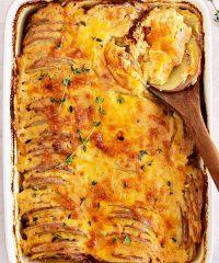 Potatoes au gratin in a red casserole dish