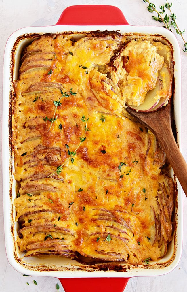 Potatoes au gratin in a red casserole dish